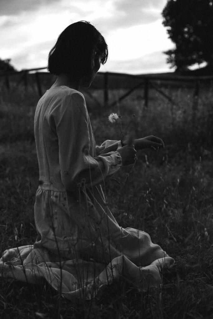 Modella con fiore in mano bianco e nero fotografia low key
