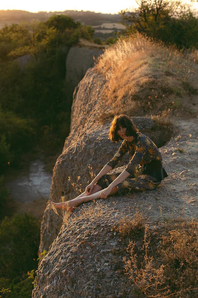 Fashion editorial tramonto modella in controluce su una roccia
