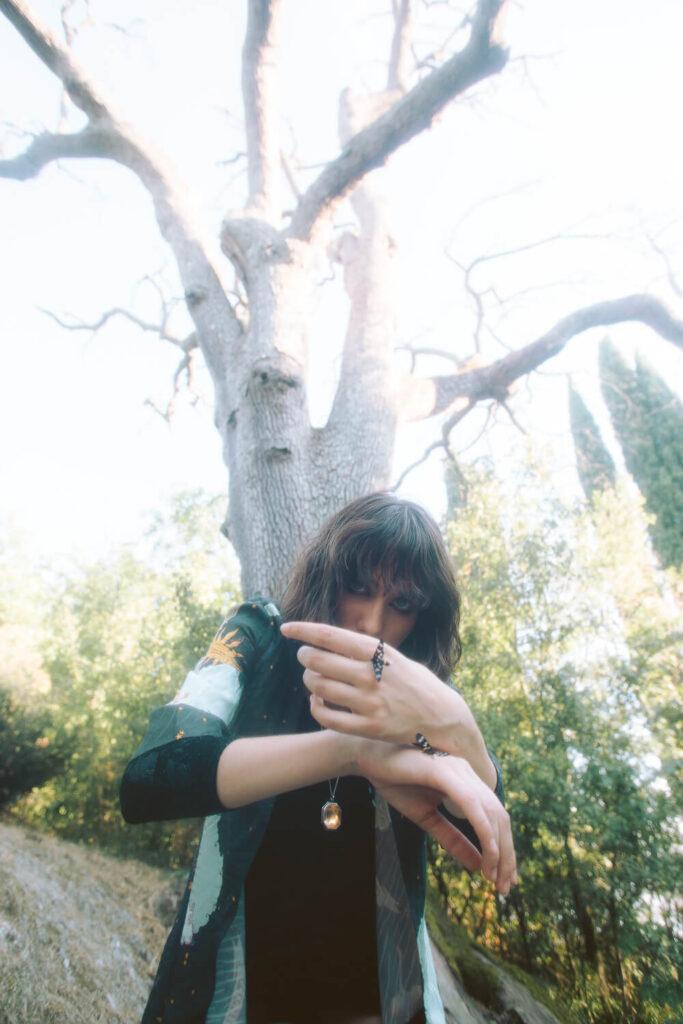 ragazza nel bosco con farfalla falena nera sulla mano